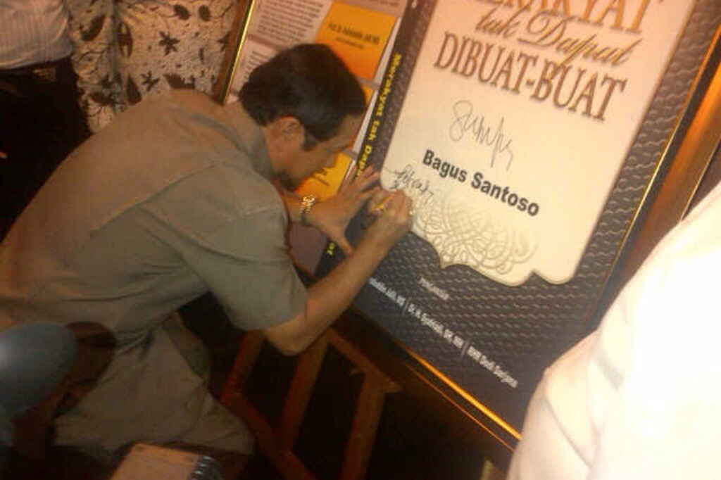 Dr. H. Syafriadi, SH, MH menandatangani cover buku karya Bagus Santoso